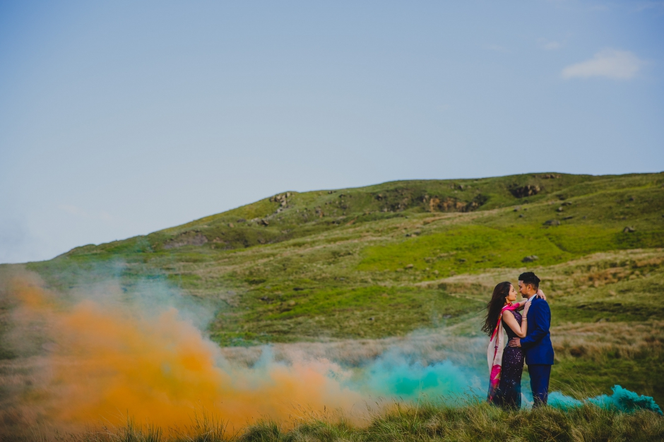Couple on mountain with smoke bombs