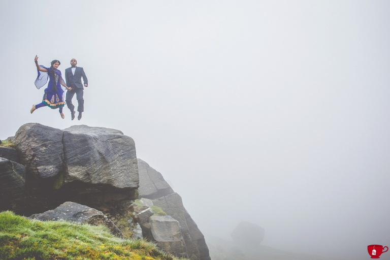 Couple jumping on a cliff during a foggy day in Yorkshire